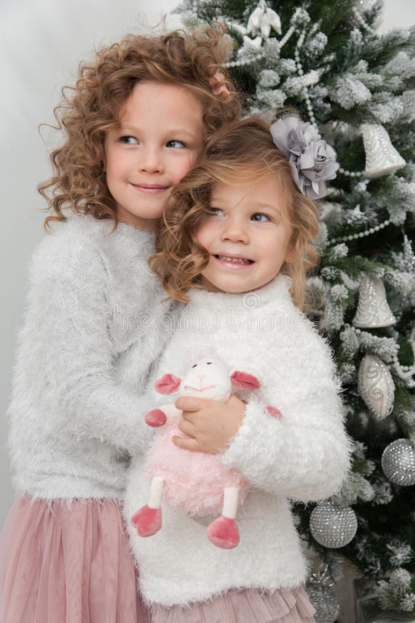 As meninas bonitos da criança com brinquedo dos carneiros estão a árvore de Natal próxima imagens de stock royalty free
