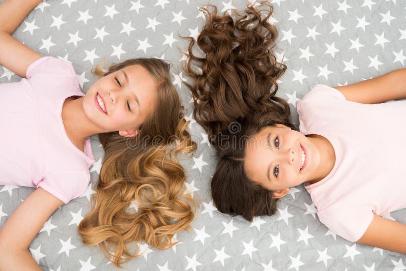 As meninas com cabelo encaracolado longo colocam na opinião superior da cama As crianças aperfeiçoam os olhares encaracolado do p foto de stock