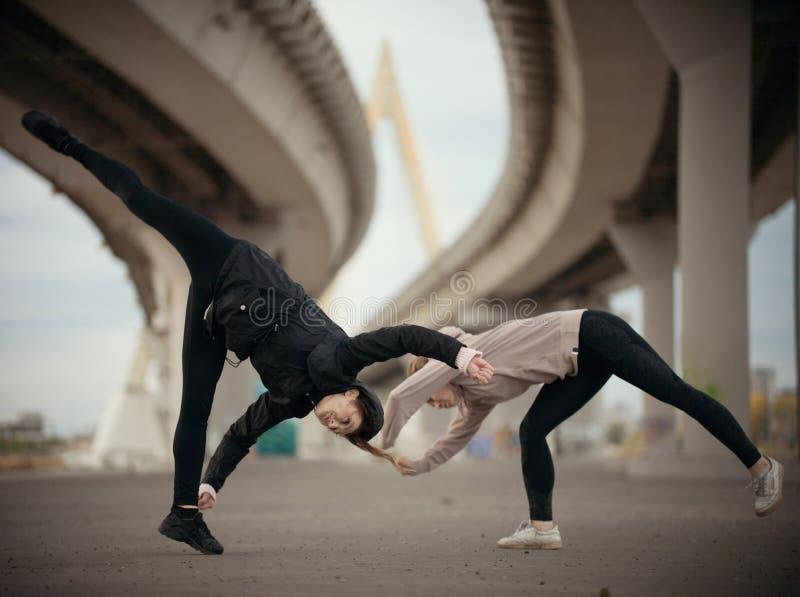 As meninas começam a executar um salto sincronizado nas separações no fundo urbano da ponte imagens de stock royalty free