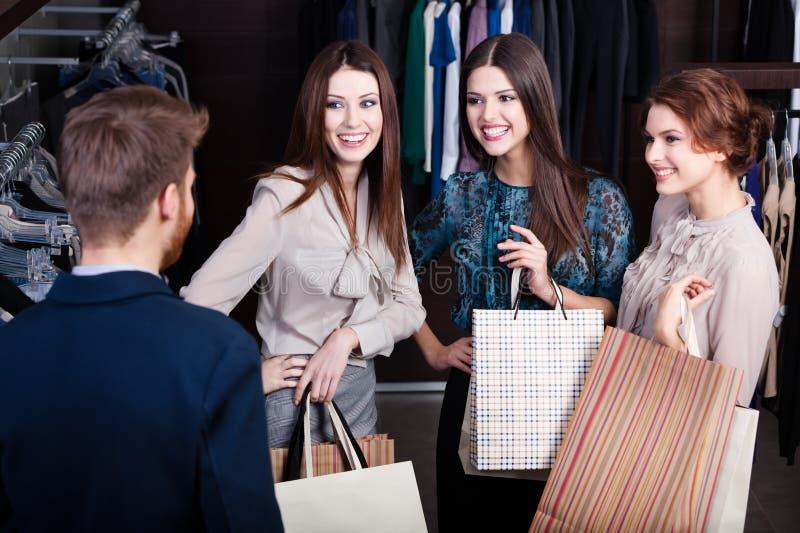 As meninas consultam com o assistente de loja fotografia de stock