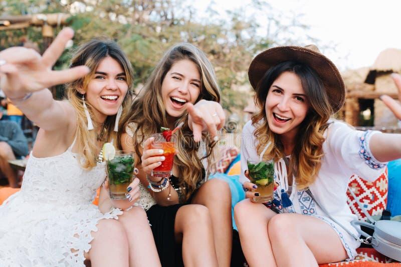 As meninas de cabelos compridos atrativas em vestuários e em acessórios à moda bebem cocktail e levantamento com ondulação das mã foto de stock royalty free
