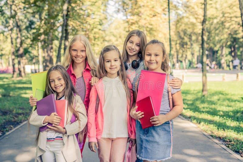 As meninas de sorriso bonitas est?o junto no parque da luz do sol imagem de stock royalty free