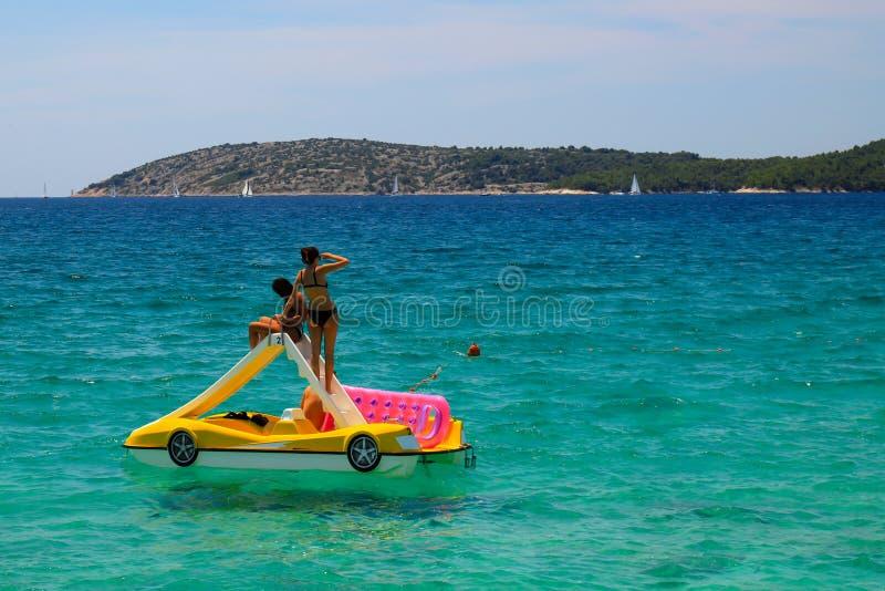 As meninas delgadas nos maiôs flutuam em um barco inflável no mar bonito em Sibenik, Croácia, praia croata, resto fotografia de stock royalty free