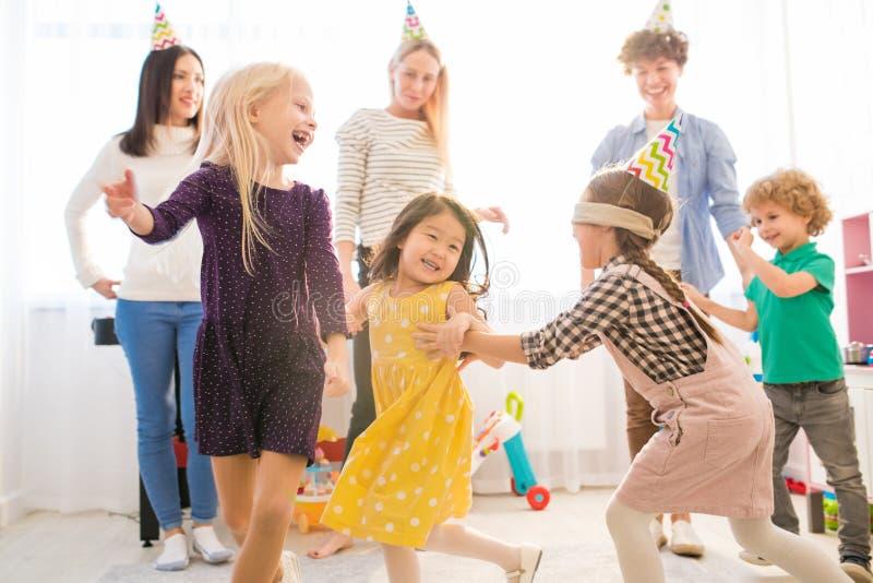 As meninas despreocupadas que correm ao jogar cortinas equipam o lustre fotos de stock