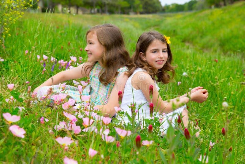 As meninas dos amigos das crianças na papoila da mola florescem o prado foto de stock