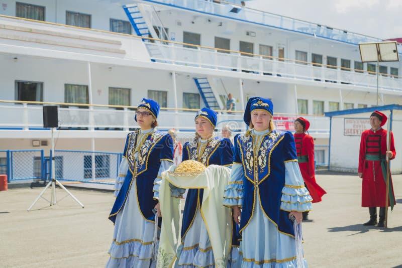 As meninas e as mulheres em vestidos nacionais encontraram passageiros do navio imagem de stock royalty free