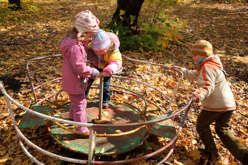 As meninas e o menino jogam no carrossel no parque outonal imagem de stock royalty free