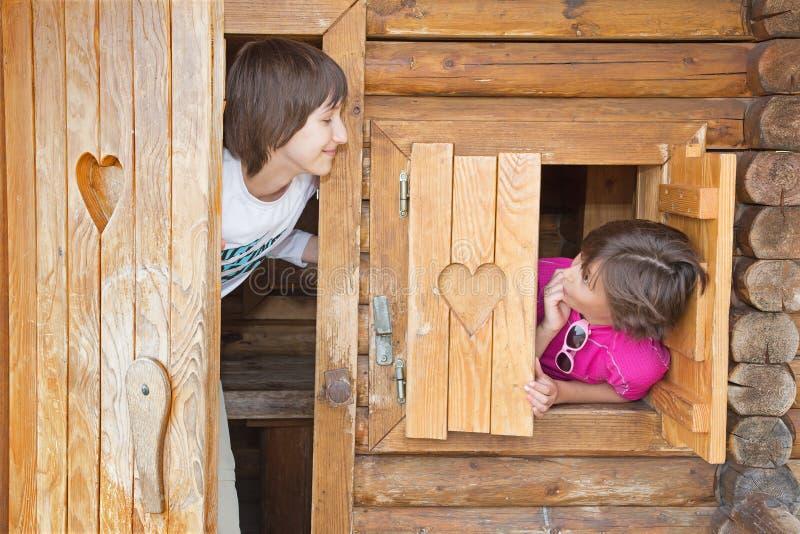 As meninas em pouca casa de campo de madeira imagens de stock royalty free