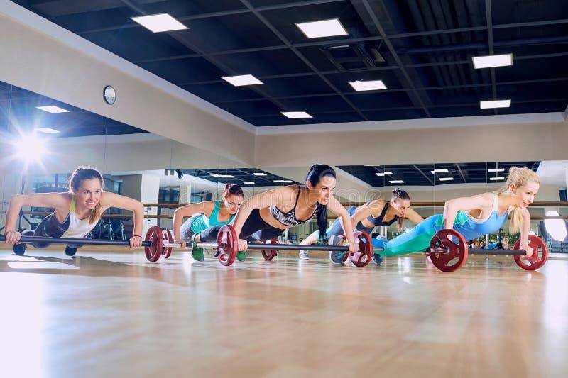 As meninas empurram levantam do assoalho no gym treinamento do grupo imagem de stock