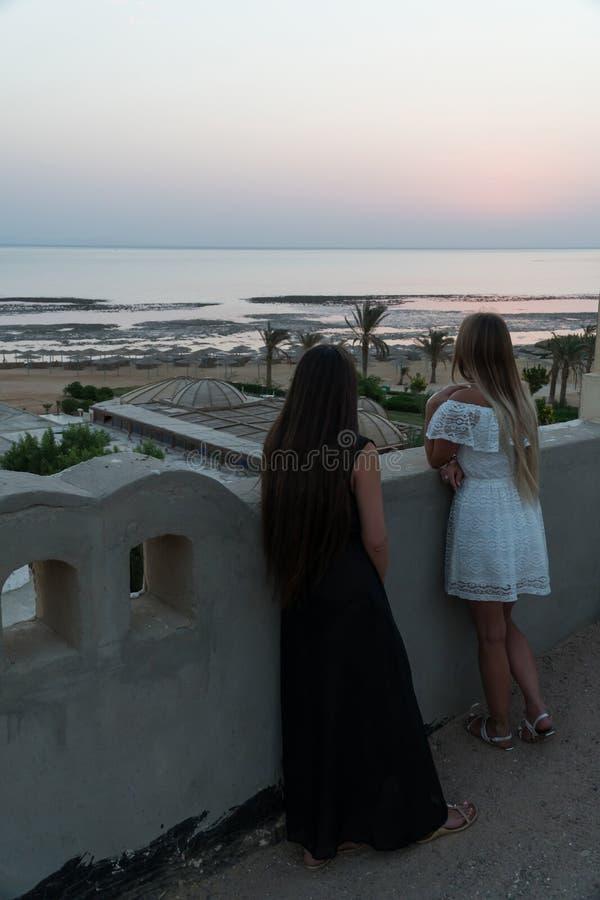 As meninas encontram o alvorecer no telhado da construção fotografia de stock royalty free