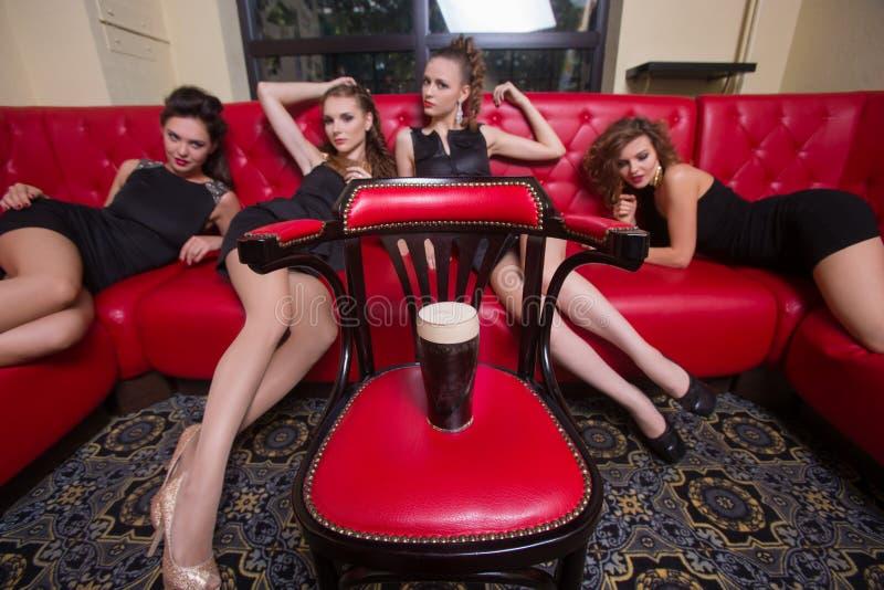 As meninas encontram-se no sofá para um vidro da cerveja fotografia de stock royalty free