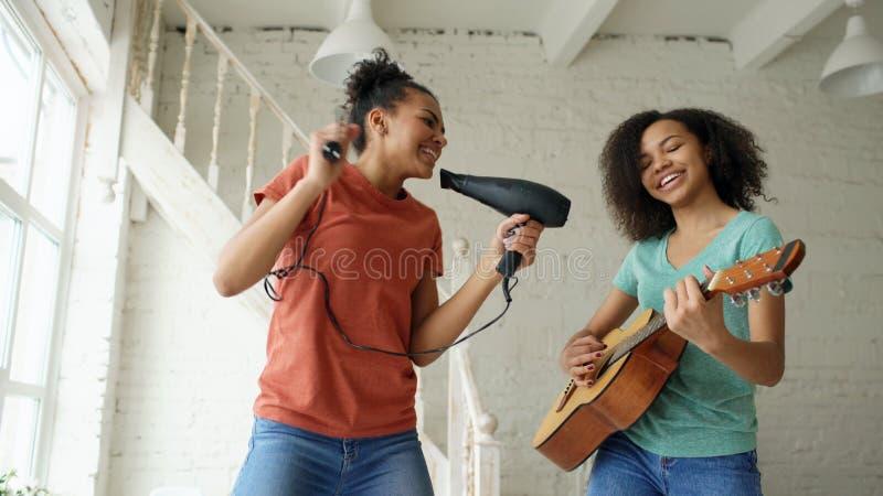 As meninas engraçadas novas da raça misturada dançam o canto com hairdryer e o jogo da guitarra acústica em uma cama Irmãs que tê imagens de stock