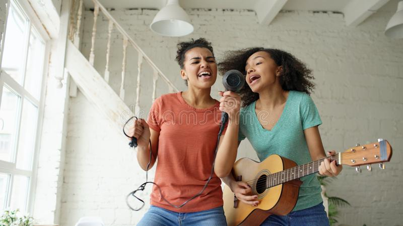 As meninas engraçadas novas da raça misturada dançam o canto com hairdryer e o jogo da guitarra acústica em uma cama Irmãs que tê foto de stock royalty free