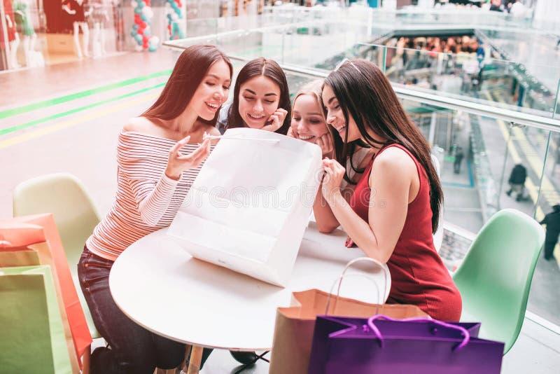 As meninas estão sentando-se na tabela e estão olhando-se no saco de compras São felizes e muito entusiasmado imagens de stock