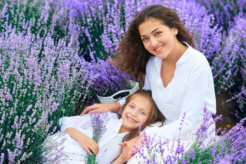 As meninas est?o no campo de flor da alfazema, paisagem bonita do ver?o imagem de stock