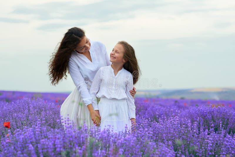 As meninas est?o no campo de flor da alfazema, paisagem bonita do ver?o foto de stock royalty free