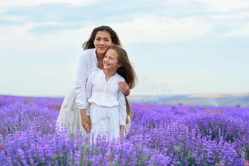 As meninas est?o no campo de flor da alfazema, paisagem bonita do ver?o imagens de stock royalty free