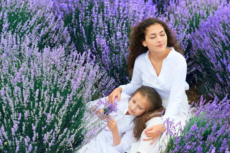 As meninas est?o no campo de flor da alfazema, paisagem bonita do ver?o imagens de stock