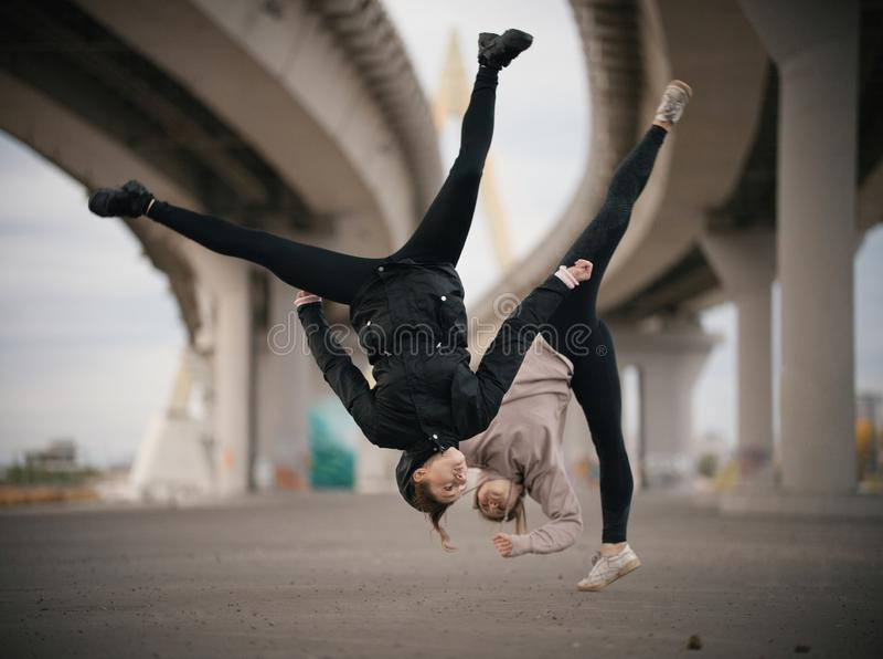 As meninas executam separações no ar ao saltar no fundo urbano da ponte fotografia de stock royalty free