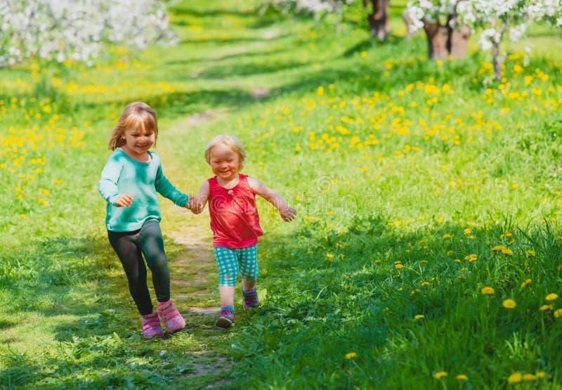 As meninas felizes jogam a corrida na natureza da mola, flor da maçã, atividades sazonais imagem de stock royalty free