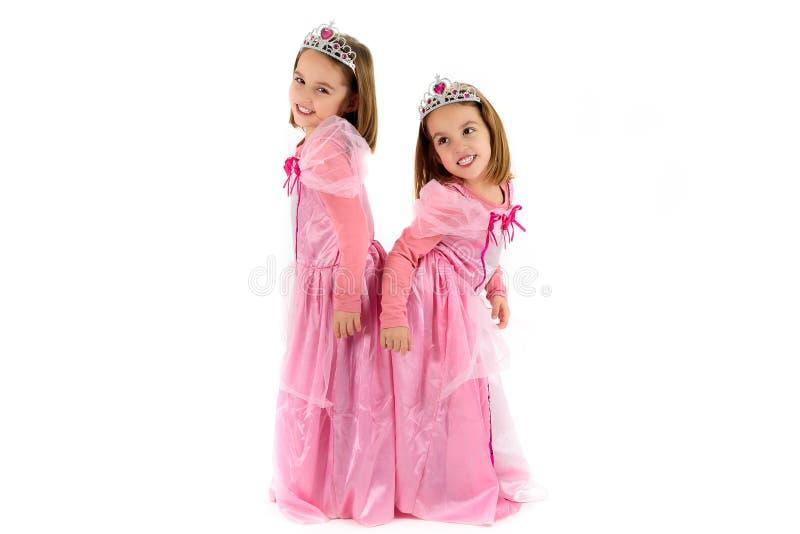 As meninas gêmeas pequenas são vestidas como a princesa no rosa imagem de stock