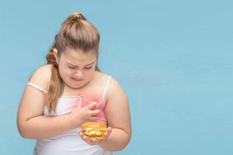 As meninas gordas sofrem da dor no cora??o dos alimentos errados s?o Hamburger Sofrimento da obesidade os problemas da inf?ncia foto de stock royalty free