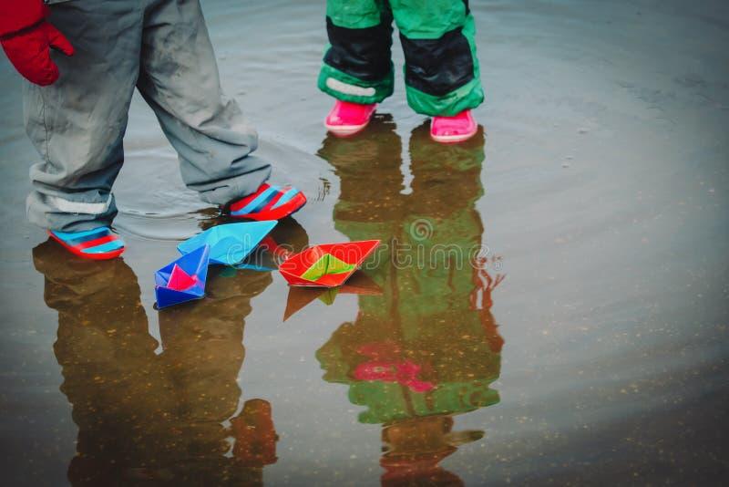 As meninas jogam com os barcos de papel na água de mola fotos de stock