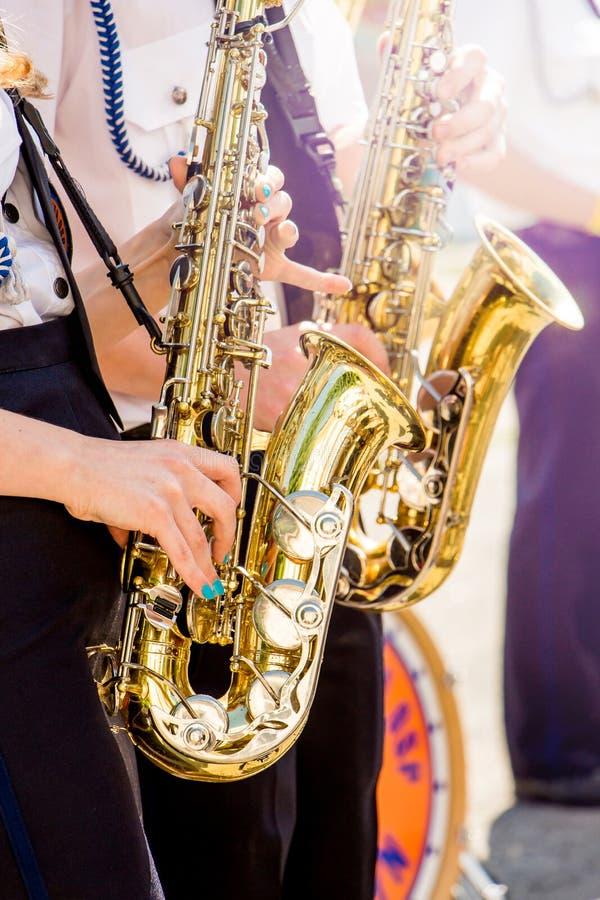 As meninas jogam saxofones no dia ensolarado claro na rua Co festivo imagem de stock