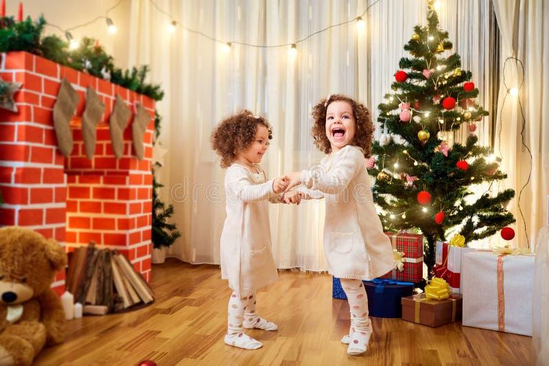 As meninas juntam a dança do Natal das crianças, tendo o divertimento, riso imagem de stock