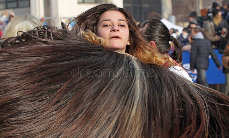 As meninas Kukeri, mummers executam espírito maus do susto dos rituais afastado durante o festival internacional de jogos do disf fotografia de stock royalty free