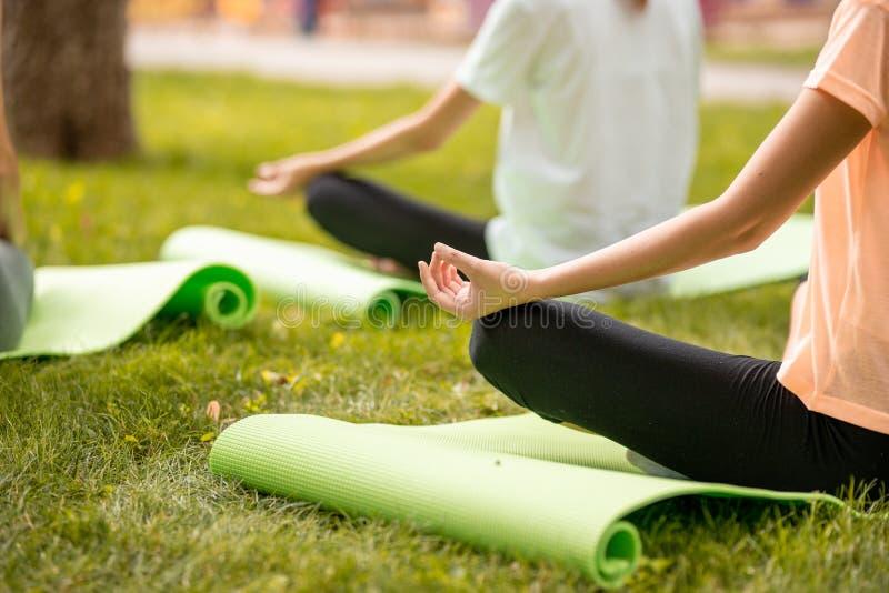 As meninas magros sentam o relaxamento na posição dos lótus que faz exercícios com outras meninas sobre a grama verde no parque e fotos de stock