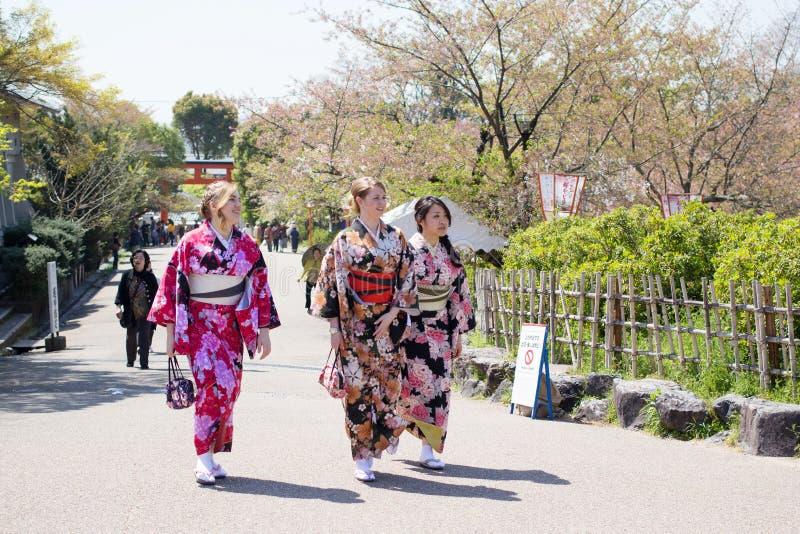 As meninas não identificadas com o terno tradicional japonês (Yukata) estão andando no parque de Maruyama fotos de stock royalty free