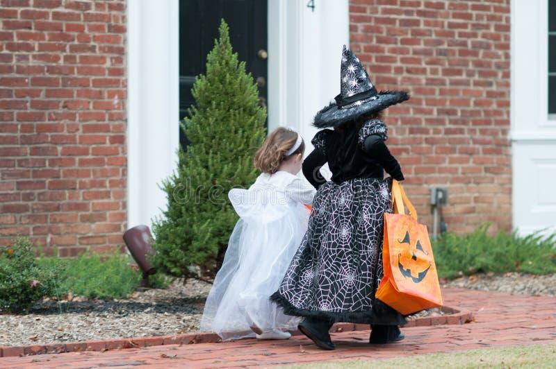 As meninas na bruxa e no fantasma trajam ter o divertimento na doçura ou travessura de Dia das Bruxas imagem de stock royalty free