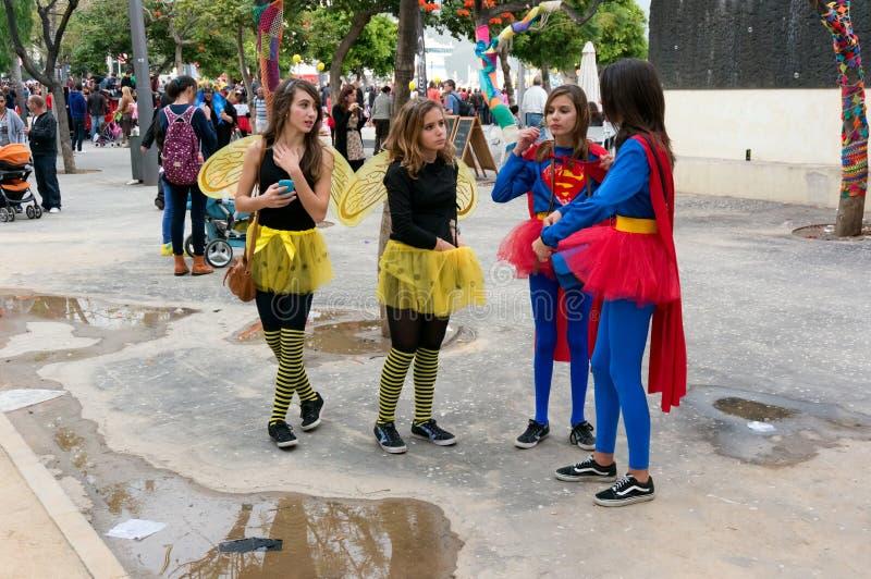 As meninas nos trajes dos insetos são estando e de fala no parque durante o carnaval anual nos desenhos animados do tema imagens de stock