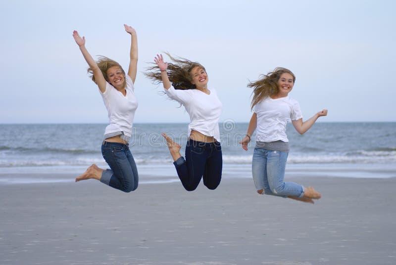 As meninas que saltam para a alegria na praia foto de stock royalty free