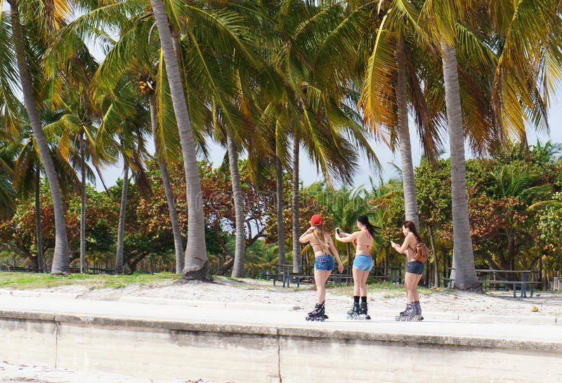 As meninas rolam na praia ensolarada do parque de Crandon fotografia de stock