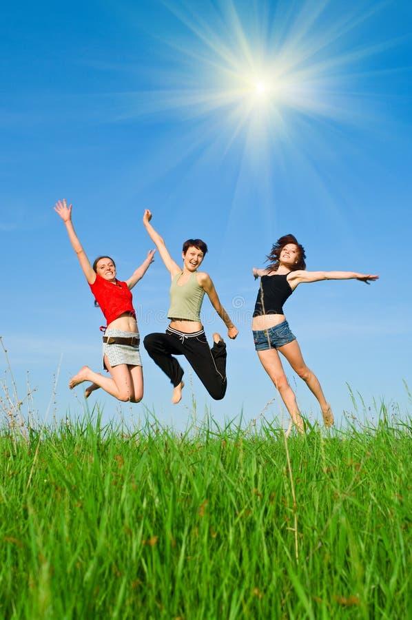 As meninas saltam no prado imagens de stock