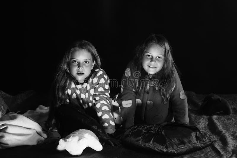 As meninas têm o partido de pijama As crianças nos pijamas sentam-se imagens de stock