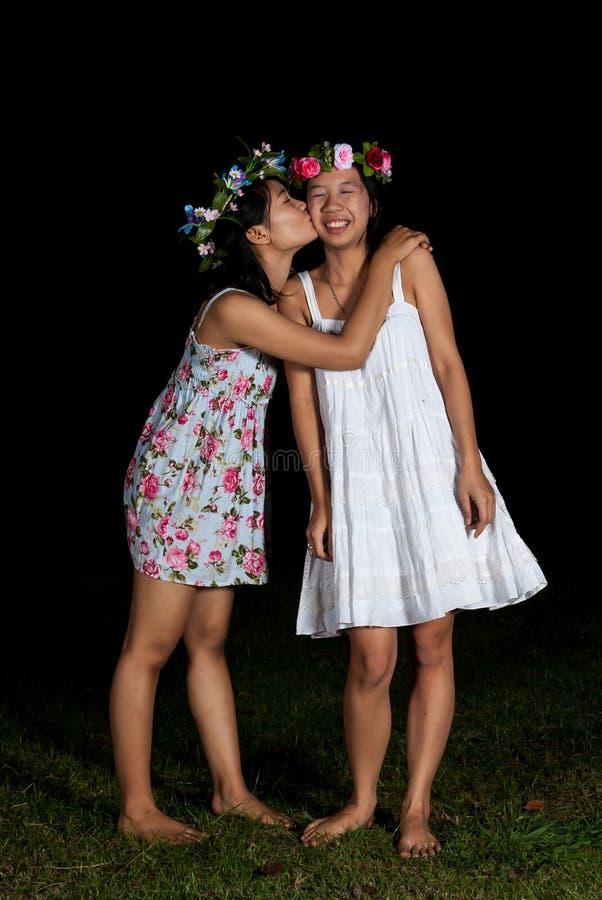 As meninas tailandesas asiáticas beijam o mordente no sentimento da amizade foto de stock