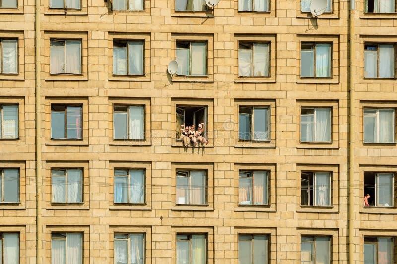 As meninas tomam sol na janela da pensão fotos de stock royalty free