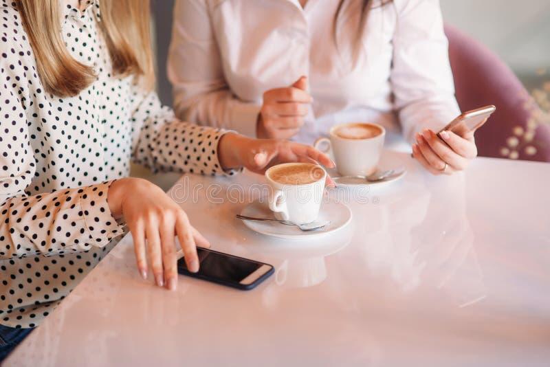 As meninas usam sua ruptura do trabalho para beber o café e o bate-papo Cappuccino de Caffe fotografia de stock