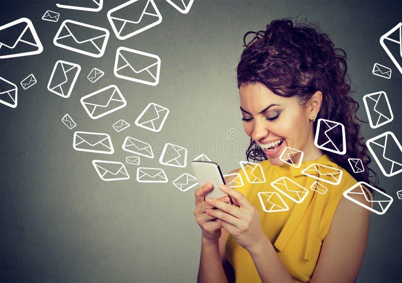 As mensagens de emissão ocupadas da mulher no telefone esperto enviam por correio eletrónico os ícones que voam para fora fotografia de stock