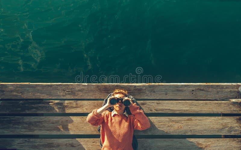 As mentiras bonitas novas da menina em Pier Near The Sea And olham através dos binóculos no céu Conceito da viagem da busca do cu fotografia de stock