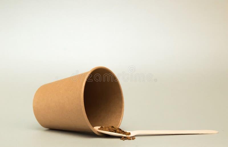 As mentiras vazias de papel do copo de caf? em um fundo claro, s?o em seguida uma colher de madeira com caf? imagem de stock royalty free