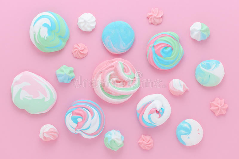 As merengues nas cores pastel, modelam o sumário no fundo cor-de-rosa foto de stock royalty free