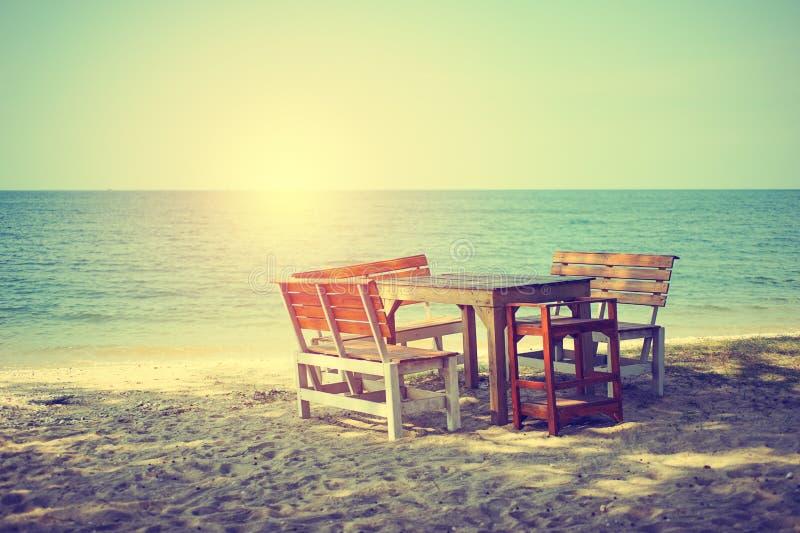 As mesas e as cadeiras de madeira na praia com sol iluminam-se fotos de stock