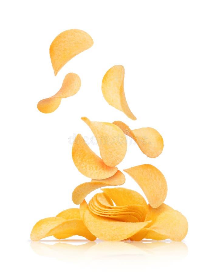 As microplaquetas de batata caem em um montão com microplaquetas em um fundo branco fotografia de stock