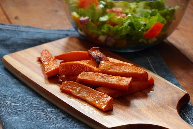 As microplaquetas de batata doce fritam e salada em uma placa de desbastamento de madeira imagens de stock royalty free