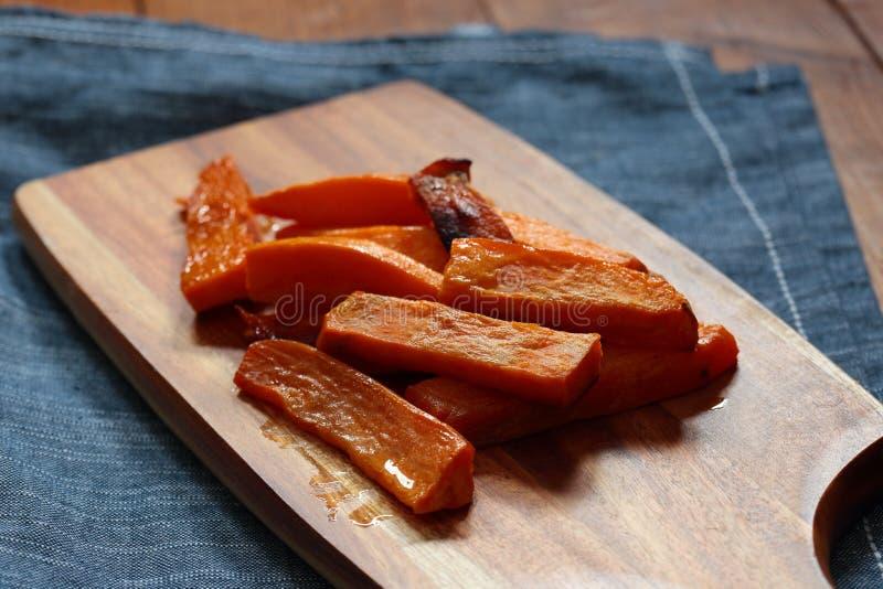 As microplaquetas de batata doce fritam em uma placa de desbastamento de madeira fotografia de stock