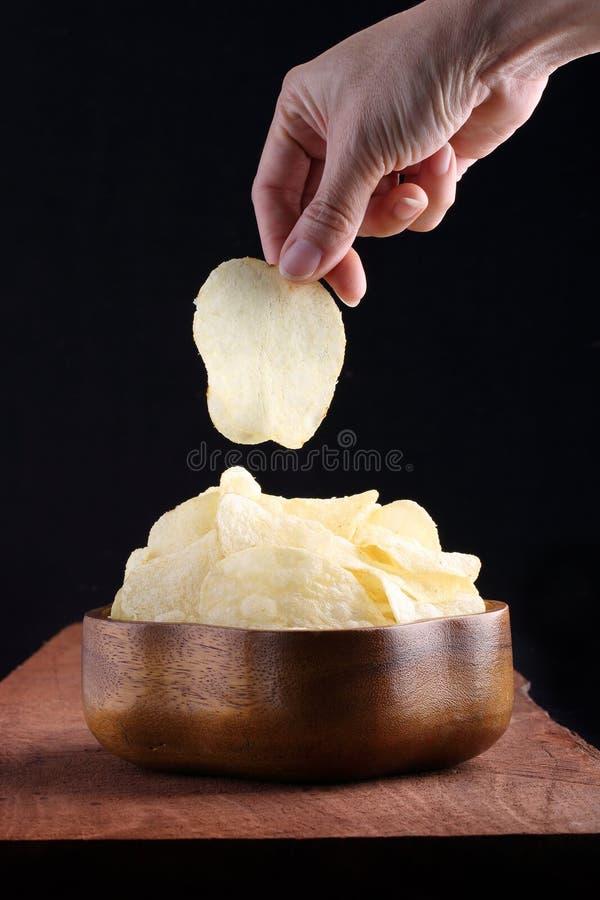 As microplaquetas de batata friáveis na bacia de madeira com mão escolheram no tr de madeira imagens de stock royalty free